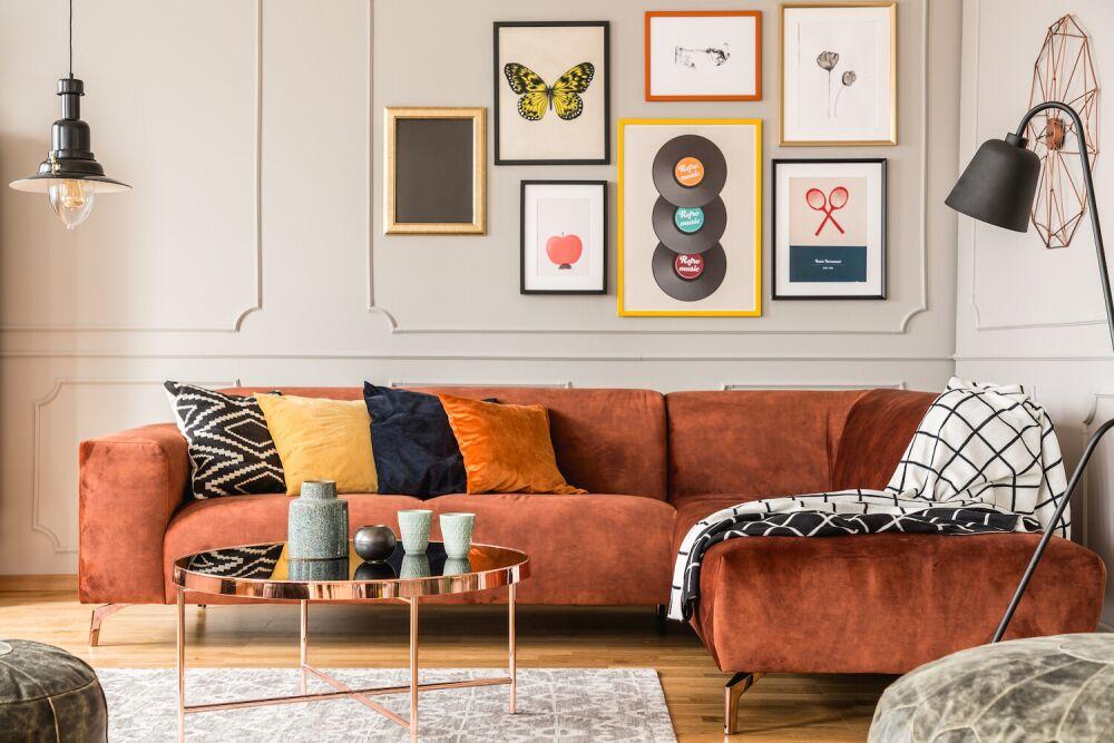 eklektyczny salon, kolorowa kanapa, grafiki na ścianie w salonie