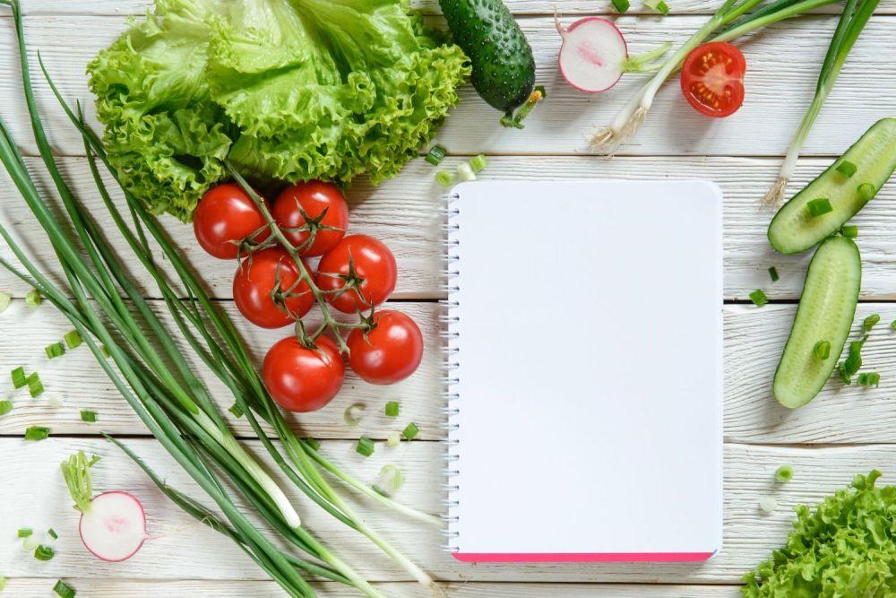 Notatnik na stole, wokół niego warzywa