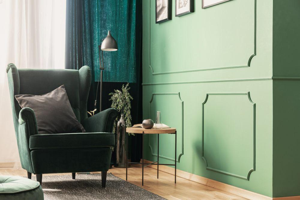 zielony salon z fotelem i zasłonami