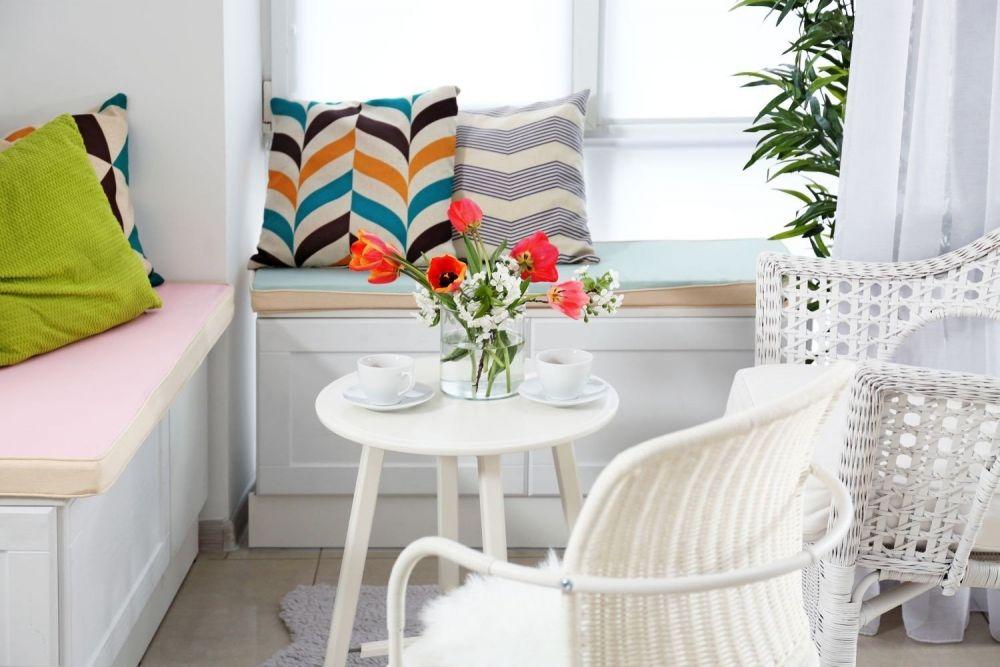 biały stolik z fotelami i siedziskami na parapecie