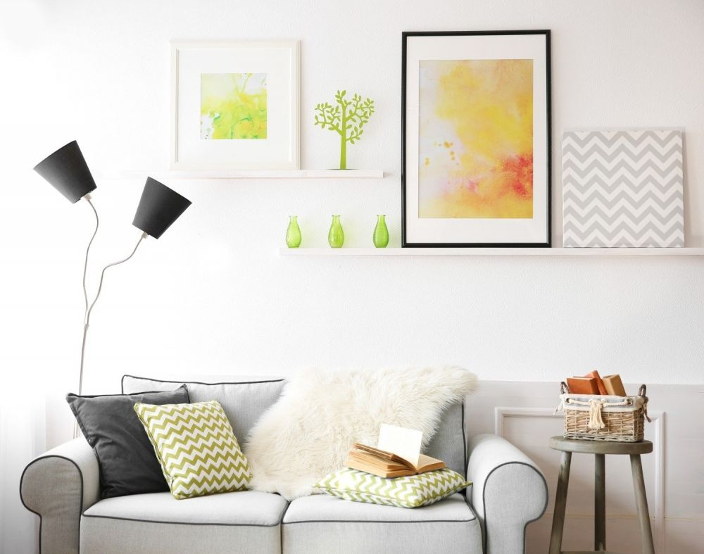 salon z kanapą z grafikami na półkach ściennych