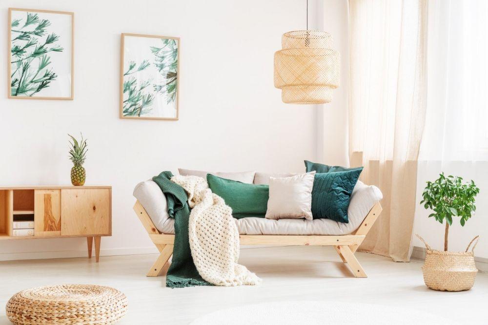 jasny salon z kanapą, drewanianymi półkami, kwiatem w doniczce i grafikami na ścianie