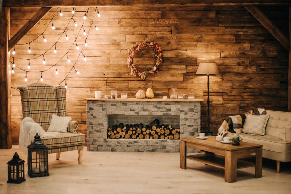 kamienny portal kominkowy z ułożonym drewnem, zimowa dekoracja, drewniane wnętrze