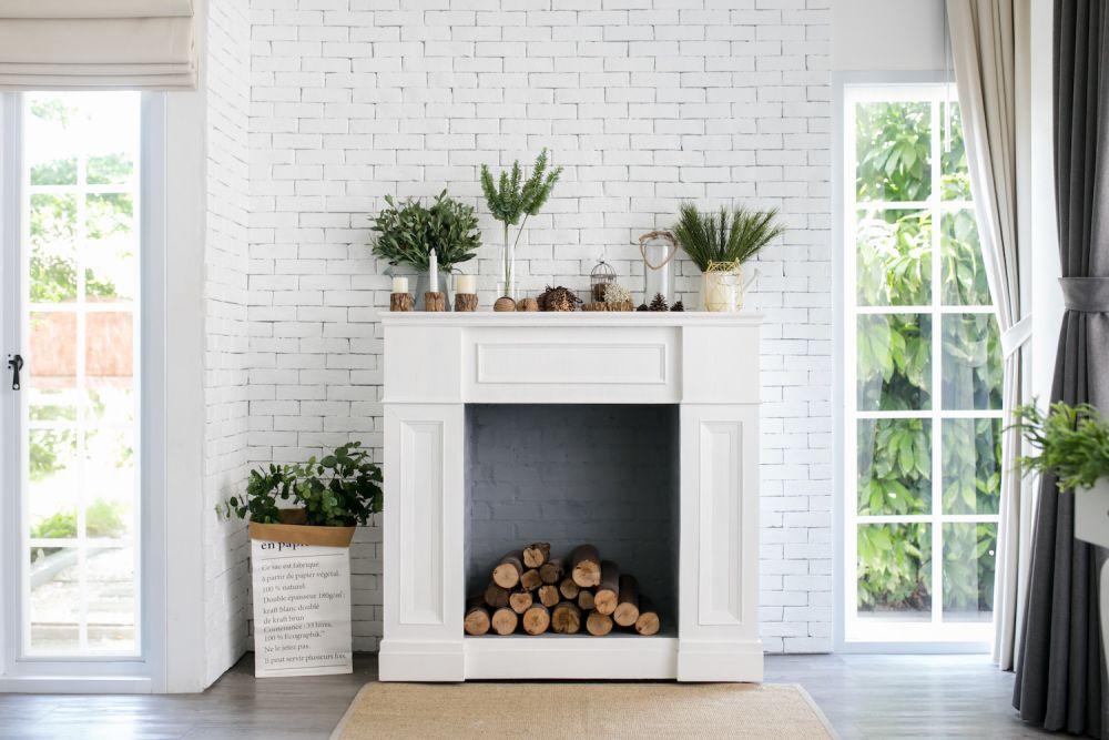 gipsowy portal kominkowy z drewnem, białe wnętrze, styl skandynawski