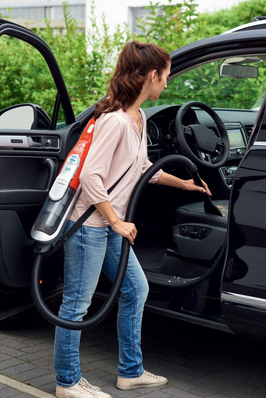 kobieta odkurzająca samochód z odkurzaczem na ramieniu
