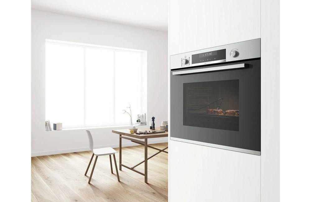 piekarnik w zabudowie bosch w białej kuchni z krzesłam, oknem i stołem