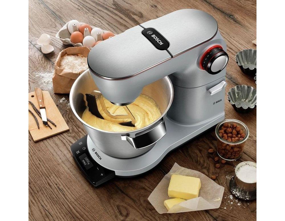 robot kuchenny na drewnianym stole wyrabiający ciasto, obok orzechy masło, mąka, jajka, foremki do ciastek