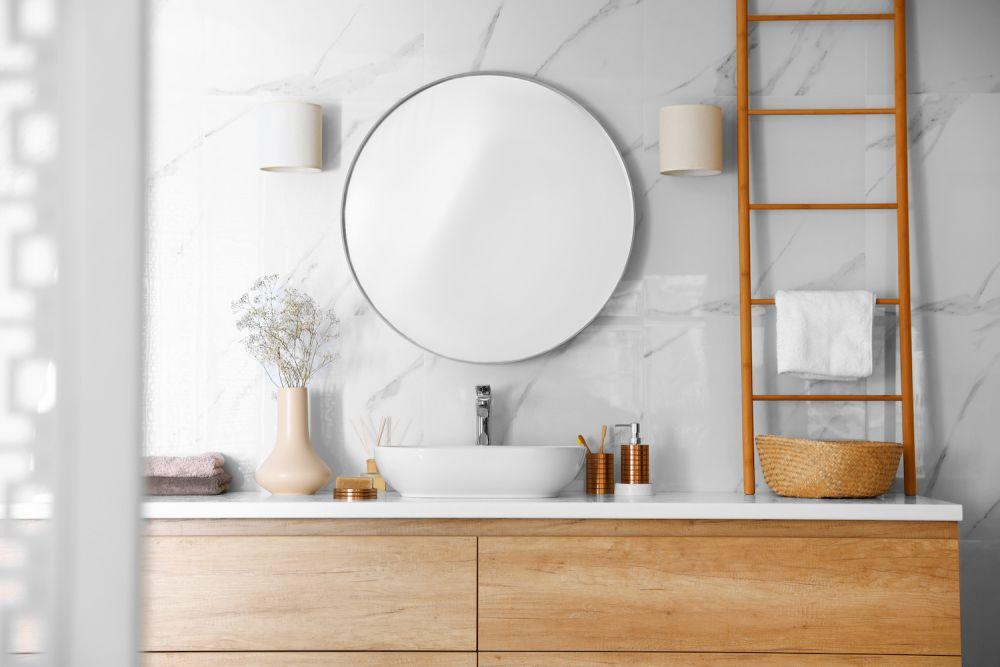 delikatne okrągłe lustro w łazience z drewnem