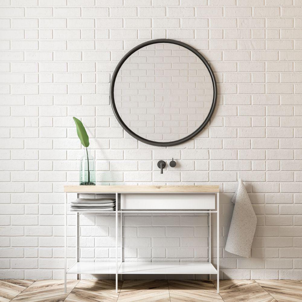 okrągłe lustro w czarnej ramie na tle białych cegieł w łazience