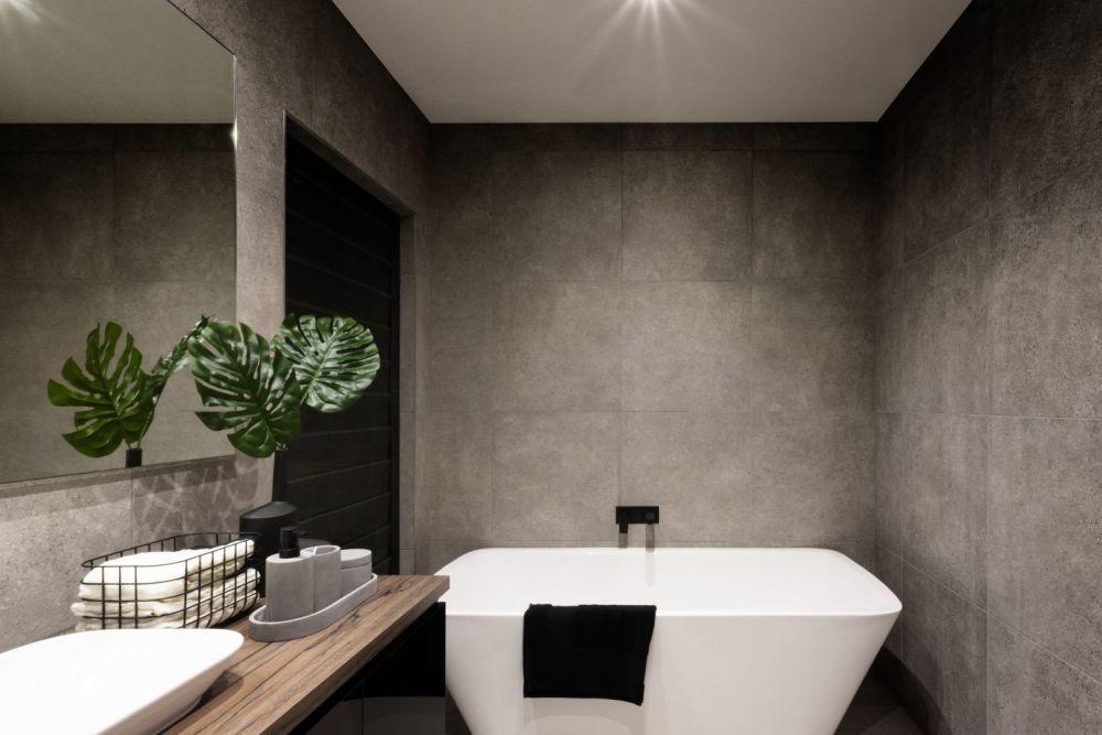 Łazienka - widok wanny i betonowych płytek na ścianach