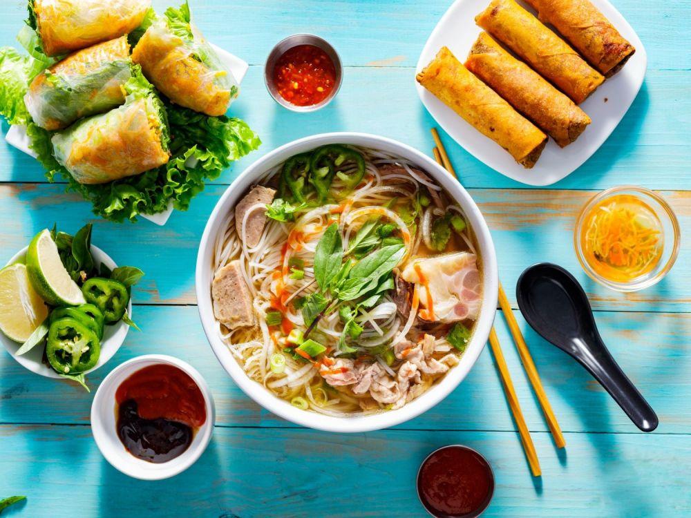 zupa pho na stole w towarzystwie wietnamskich przekąsek