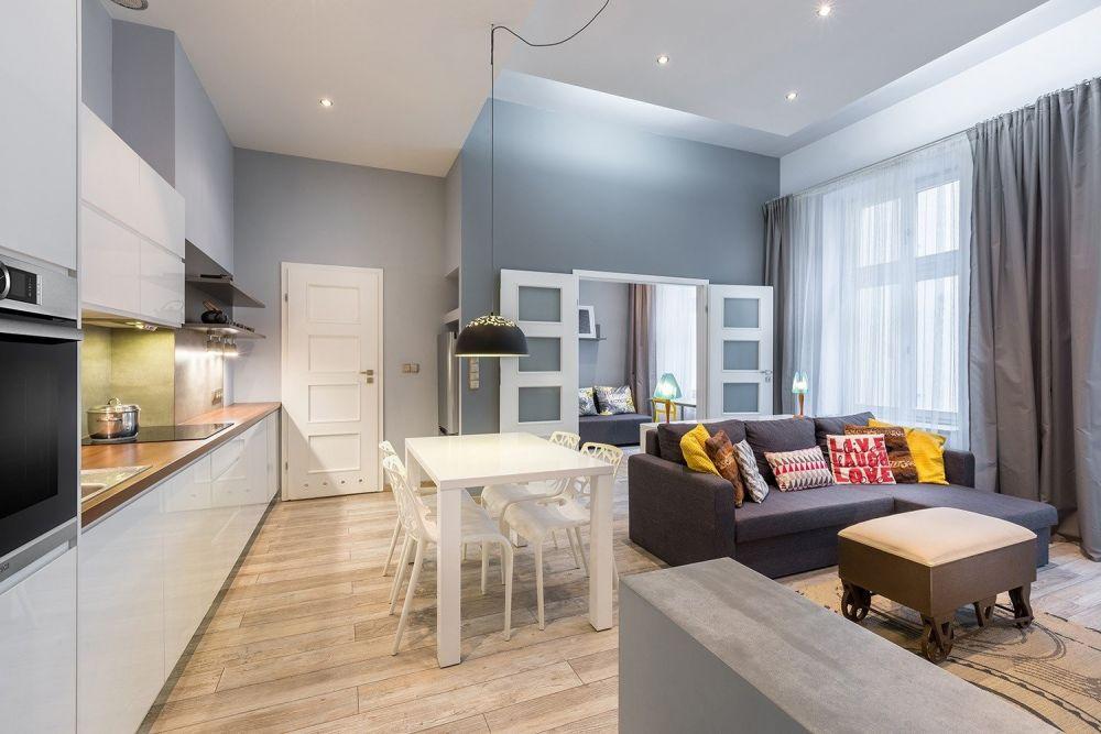 kuchnia z salonem, białym stołem i kanapą i białymi meblami w kuchni