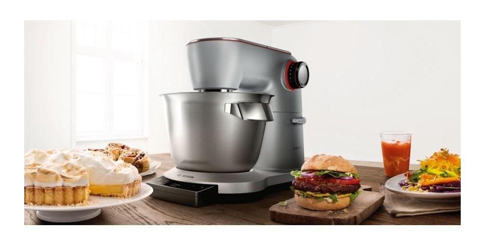 robot kuchenny na drewnianym stole z tartą, burgerami, sokiem i sałatką