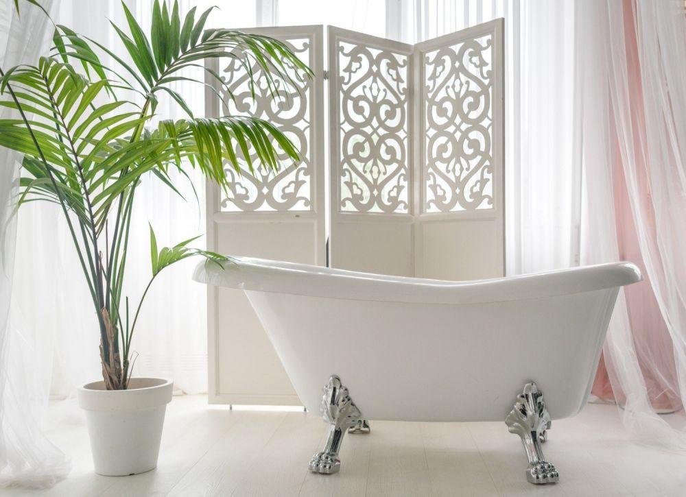 biała wanna w jasnej łazience obok kwiat w doniczce