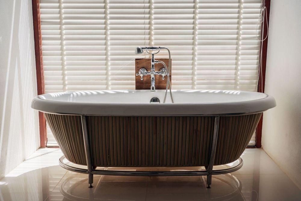 łazienka z drewnianą obudową stojąca pod oknem