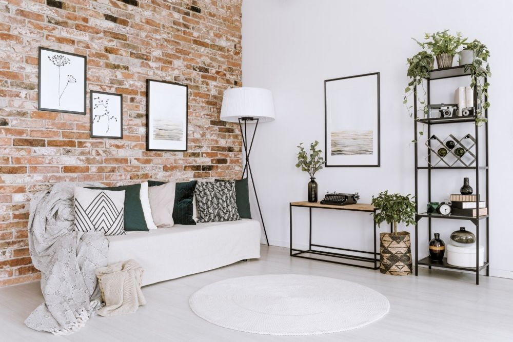 jasny salon z kanapą z półkami, lampą i zdjęciami na ścianach