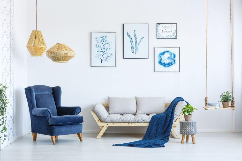 salon z kanapą, niebieskim fotelem i grafikami na ścianach