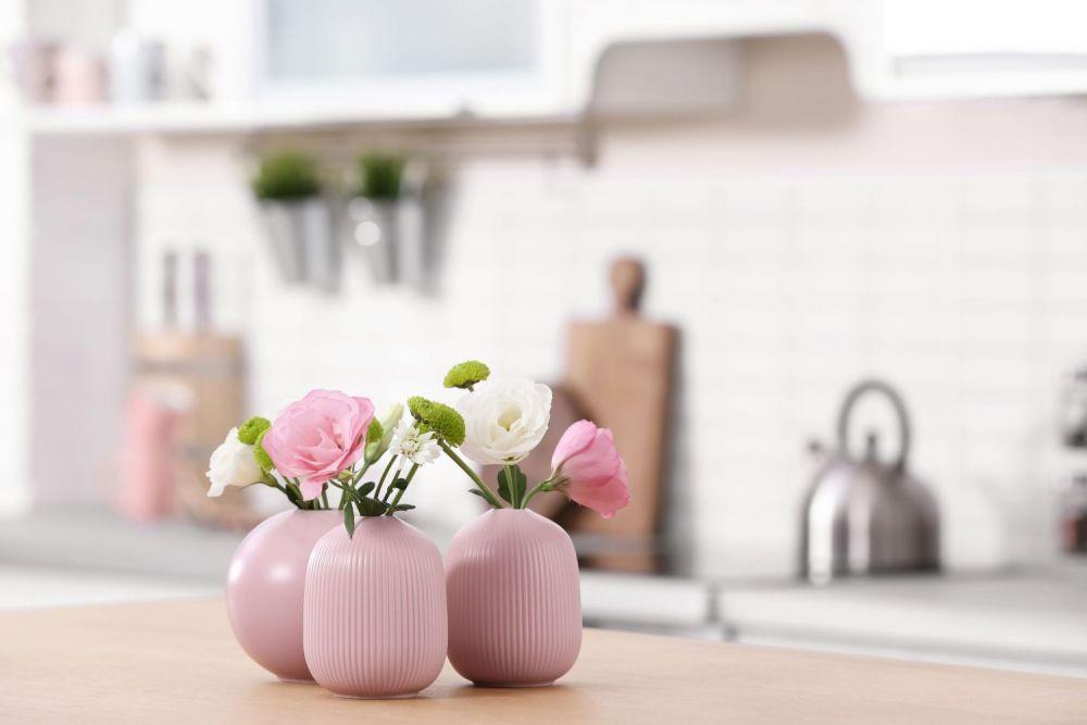 kwiaty w różowych wazonach w kuchni