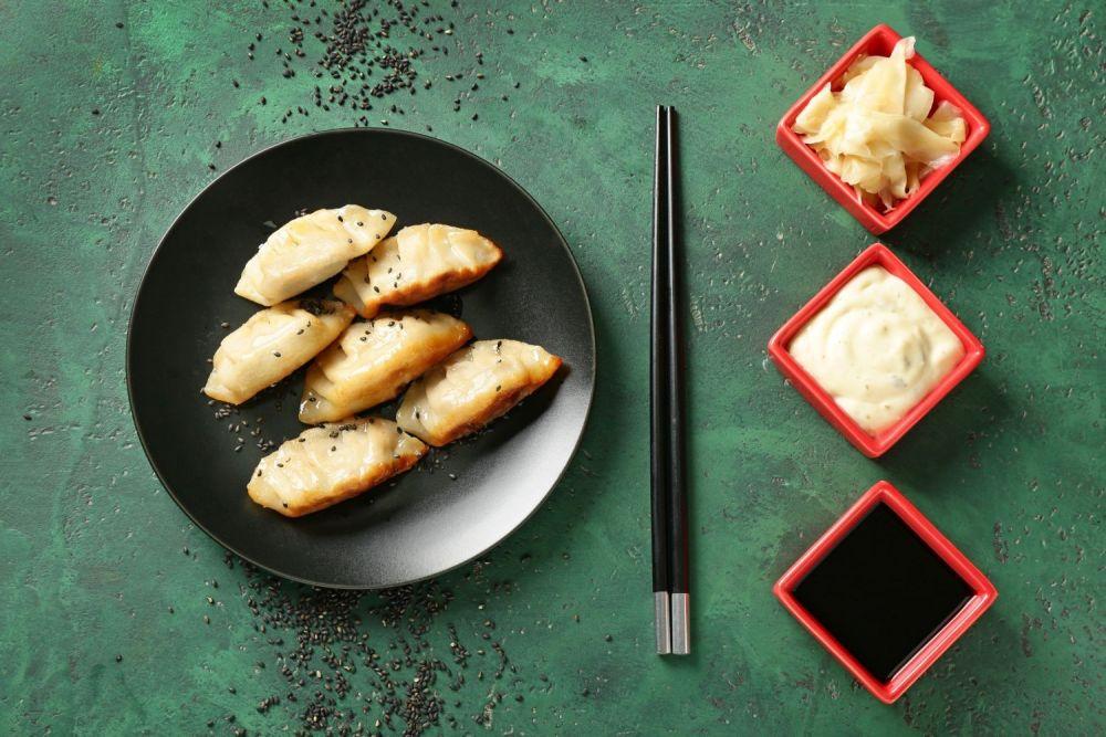 japońskie pierożki na talerzu, obok pałeczki i naczynie z sosami i imbirem