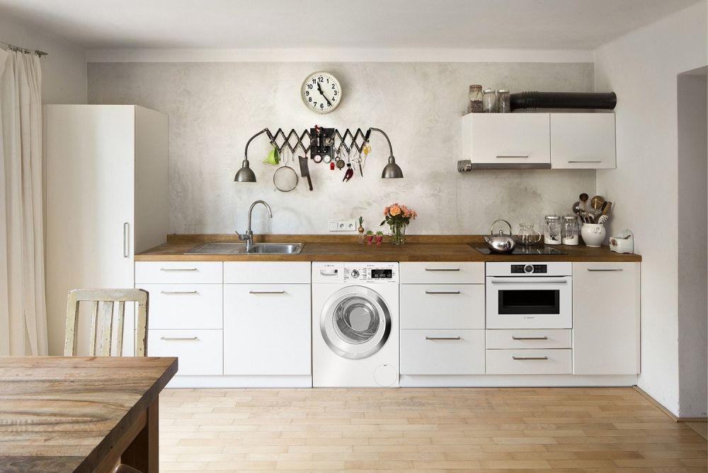biała kuchnia z drewnianym stołem i pralką w zabudowie