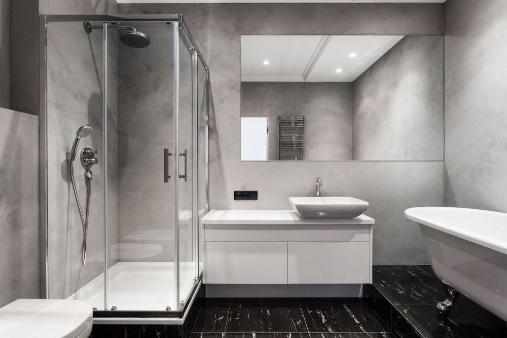 szara łazienka ze szklanym prysznicem