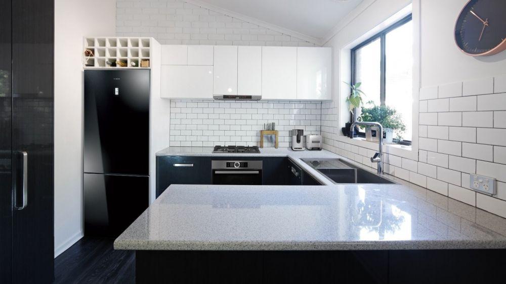 mała kuchnia z białymi blatami i czarnymi frontami