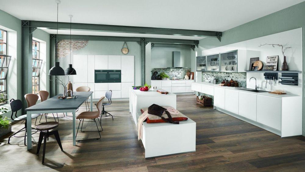 duża kuchnia z białą zabudową i stołem z krzesłami