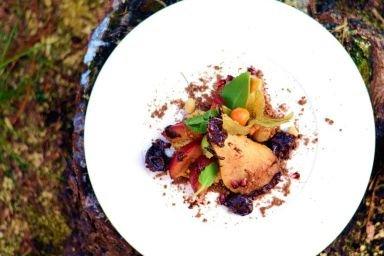 Placuszek jaglany podany na ziemi jadalnej pod pierzynką z owoców karmelizowanych z sosem czekoladowym
